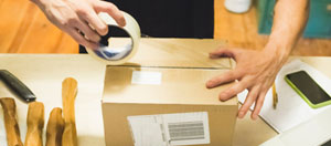 Male hands packing a small box